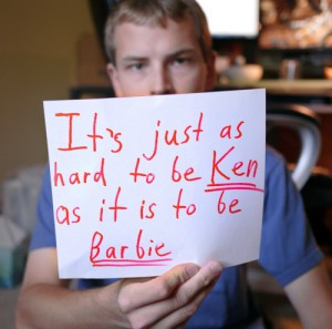 a man holding a sign that read, it's just as hard to be Ken as it is to be Barbie